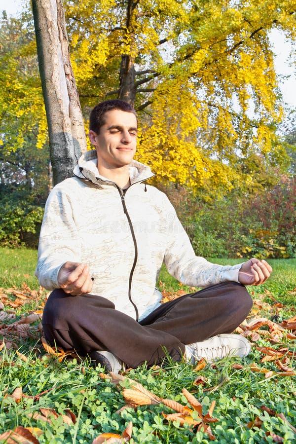 O homem novo tem meditating no parque imagens de stock
