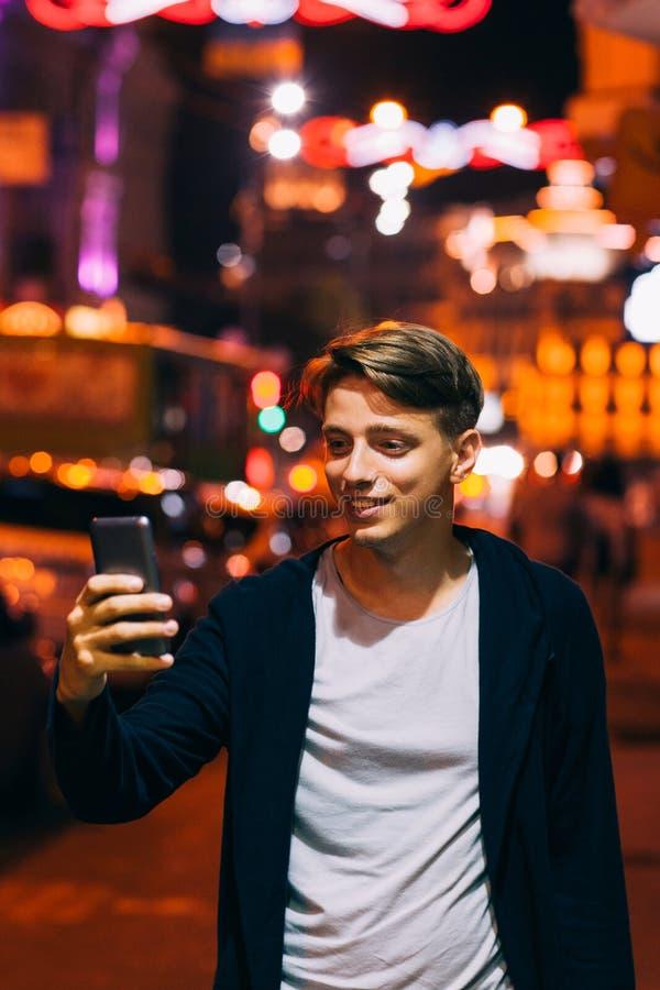 O homem novo toma a foto no smartphone na cidade fotografia de stock royalty free