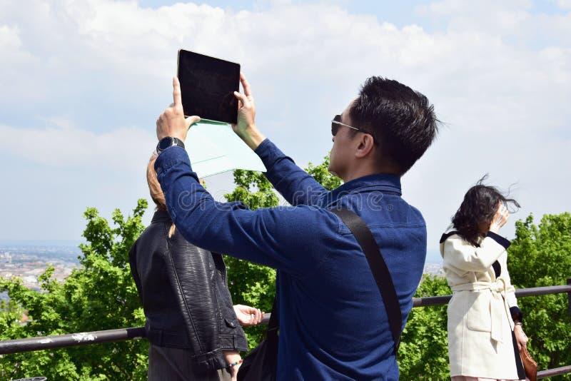 O homem novo toma uma imagem com uma tabuleta de uma vista pitoresca da cidade imagem de stock