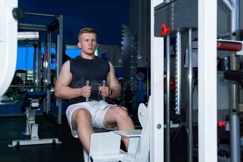 O homem novo treina os músculos da cintura de ombro e da imprensa abdominal que usa uma máquina do peso foto de stock