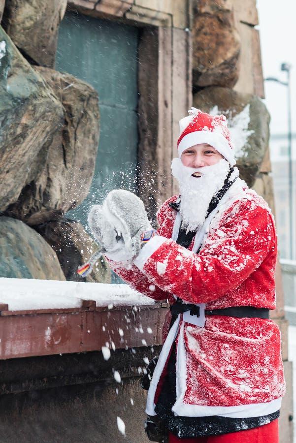O homem novo vestiu-se acima como Santa que prepara-se para jogar uma bola de neve, durante o evento Éstocolmo Santa Run da carid fotos de stock