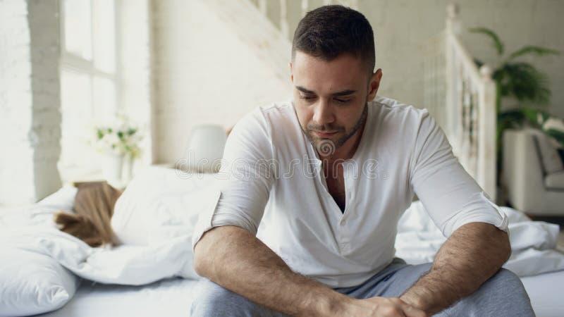 O homem novo virado que senta-se na cama sofrer dos problemas quando seu sono da amiga no quarto imagem de stock royalty free