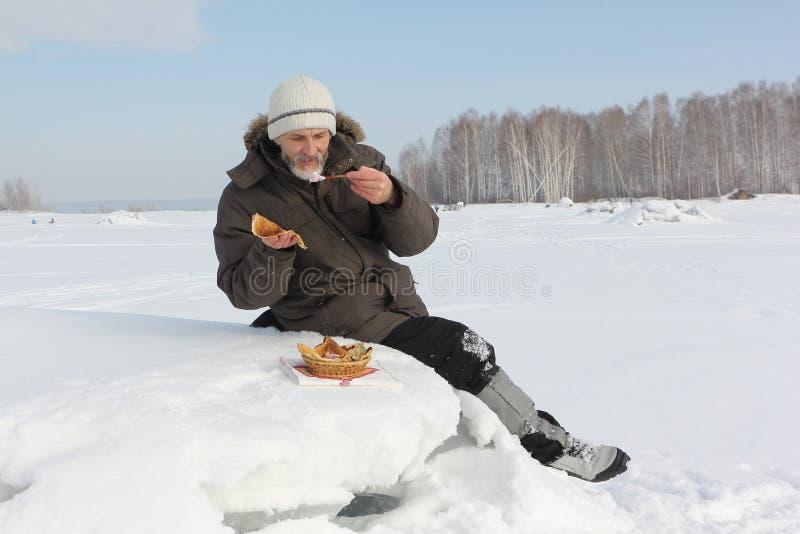 O homem o viajante com uma barba que come panquecas torradas fora foto de stock royalty free