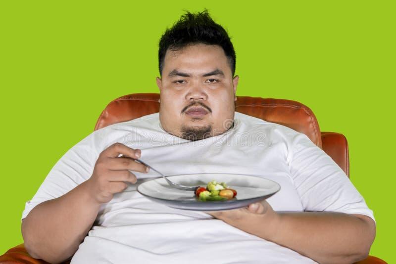 O homem obeso olha infeliz para comer a salada no estúdio fotografia de stock