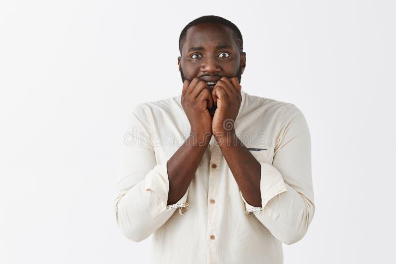 O homem obtém a audição amedrontada histórias assustadores do amigo Afro-americano atrativo intenso e nervoso assustado com curto fotos de stock