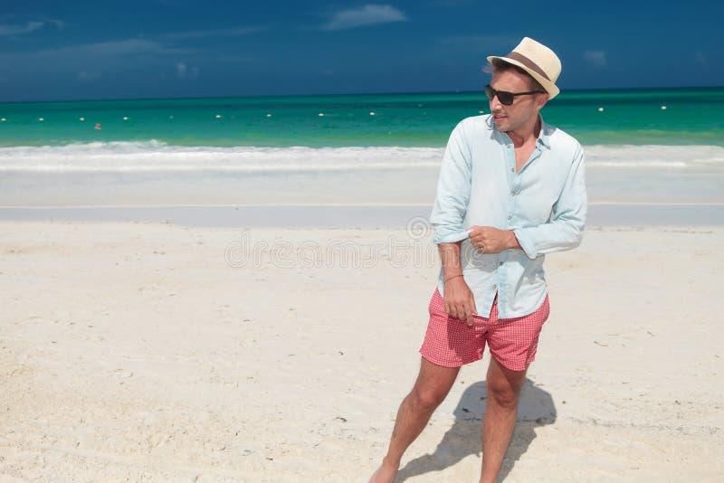 O homem ocasional anda o na praia e na luva das trações foto de stock
