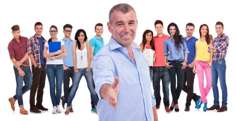 O homem ocasional idoso dá-lhe boas-vindas com um aperto de mão a sua equipe fotografia de stock royalty free
