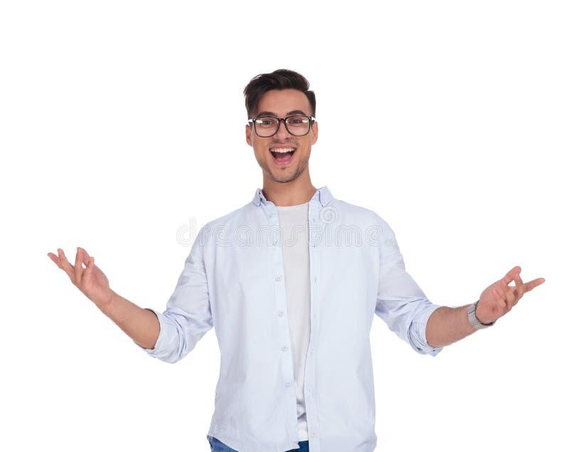 O homem ocasional novo entusiasmado com os braços estendido está gritando foto de stock