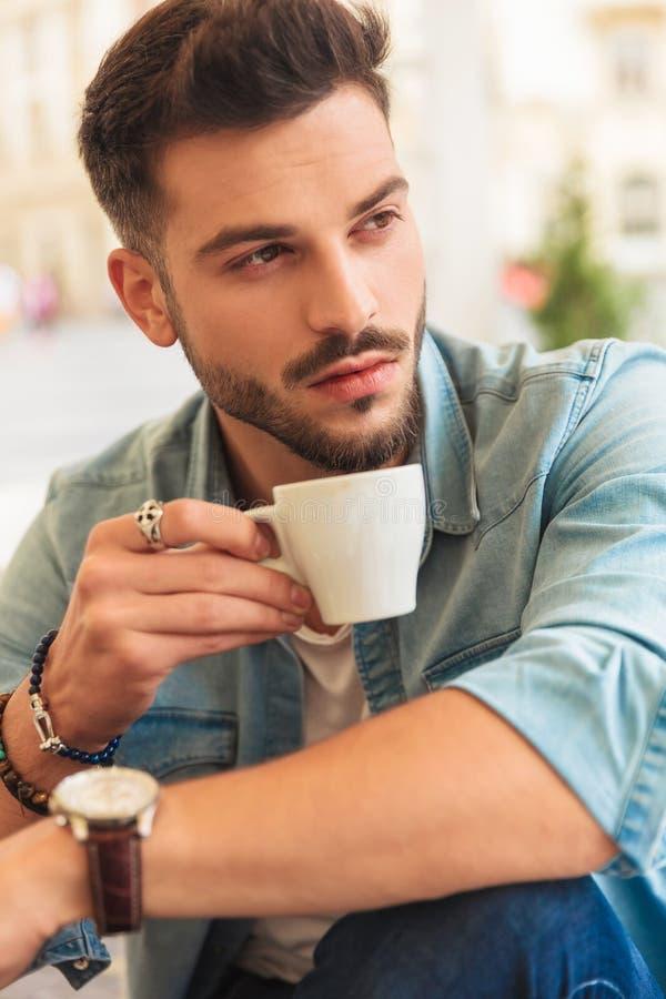 O homem ocasional sedutor toma uma ruptura e olhares de café para tomar partido fotos de stock