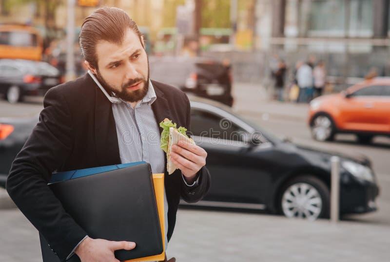 O homem ocupado é com pressa, ele não tem o tempo, ele está indo comer o petisco ir Trabalhador que come, café bebendo fotos de stock