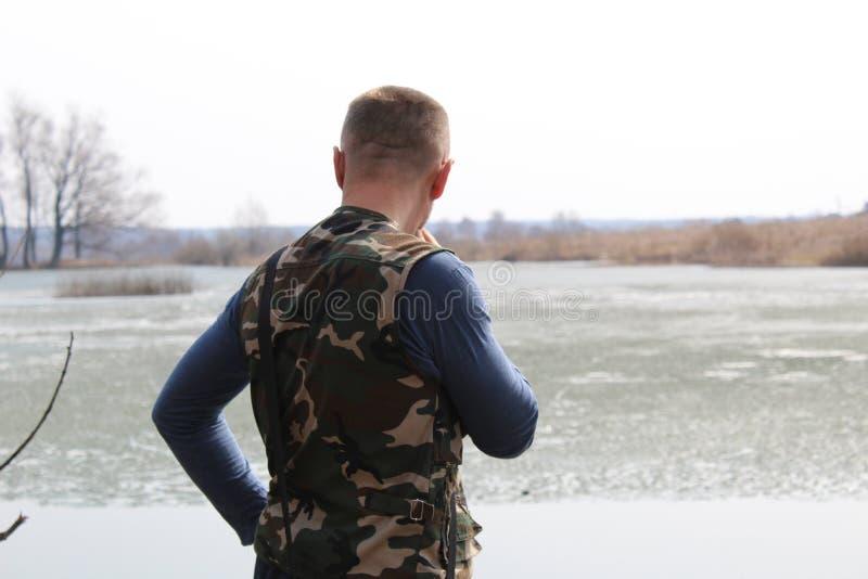 O homem olha fixamente na distância ao estar na costa do lago fotos de stock royalty free