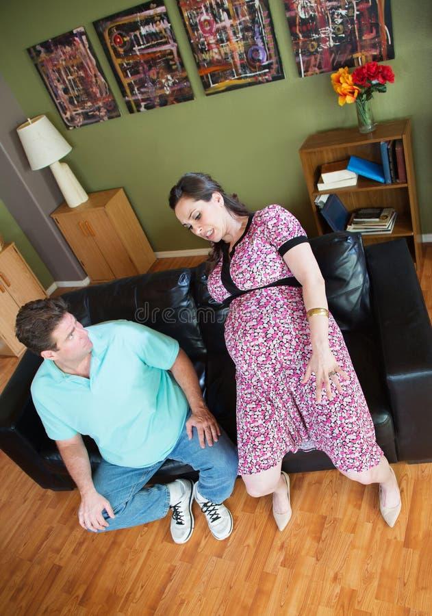 O homem olha a mulher gravida desajeitada foto de stock royalty free