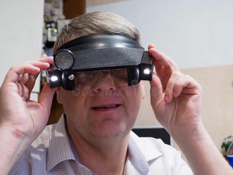 O homem olha no dispositivo ótico imagens de stock