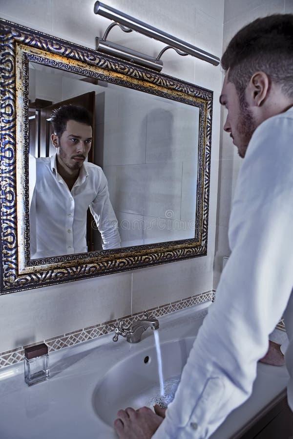 O homem olha si mesmo no espelho. foto de stock