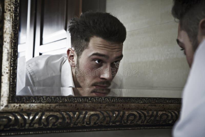 O homem olha si mesmo no espelho. foto de stock royalty free
