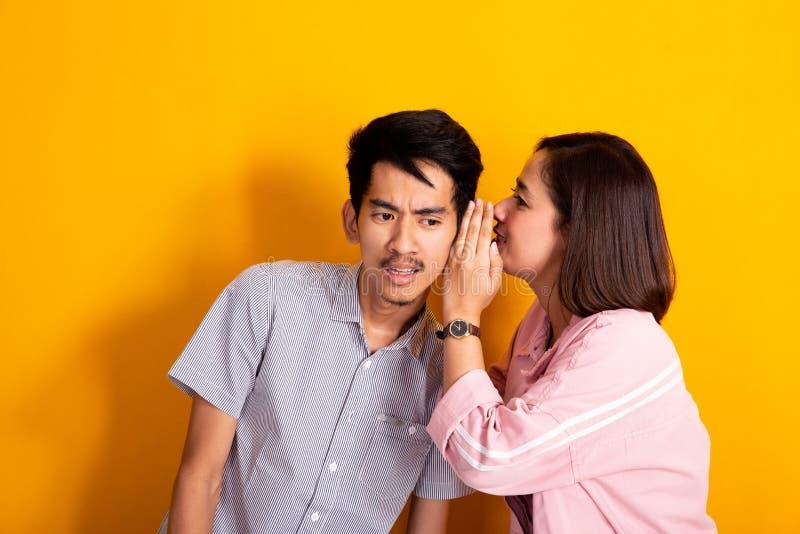 O homem olhou a mulher chocada do quando que sussurra a sua orelha fotografia de stock