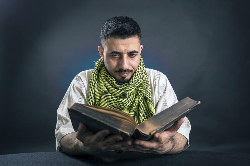 O homem oriental no vestido árabe nacional tradicional, com interesse lê o livro grande velho fotos de stock