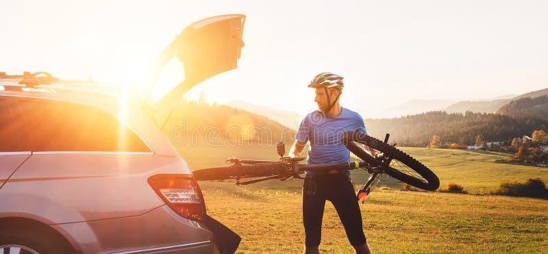 O homem pôs sua bicicleta no tronco de um carro opta o fl imagens de stock