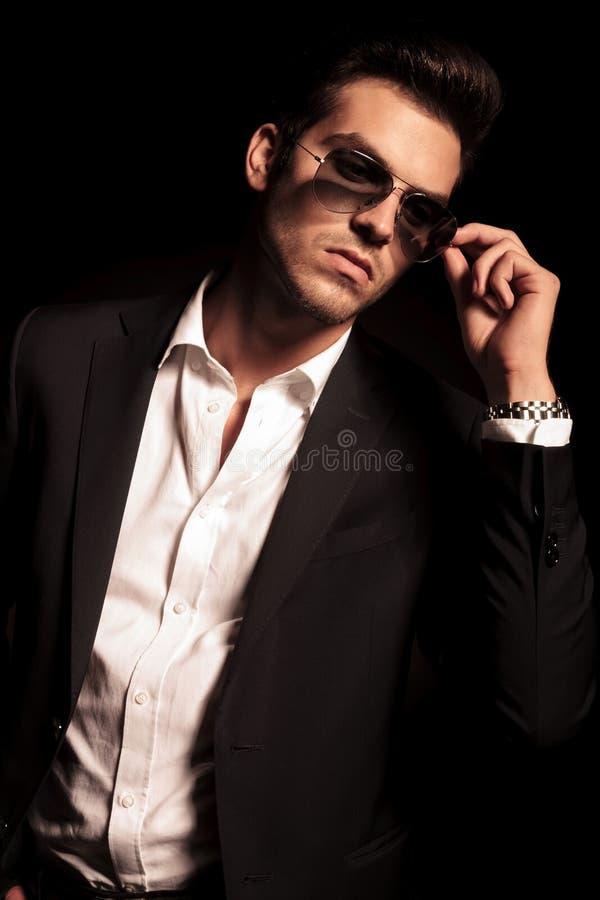 O homem põe sobre seus óculos de sol e olha para tomar partido imagens de stock royalty free