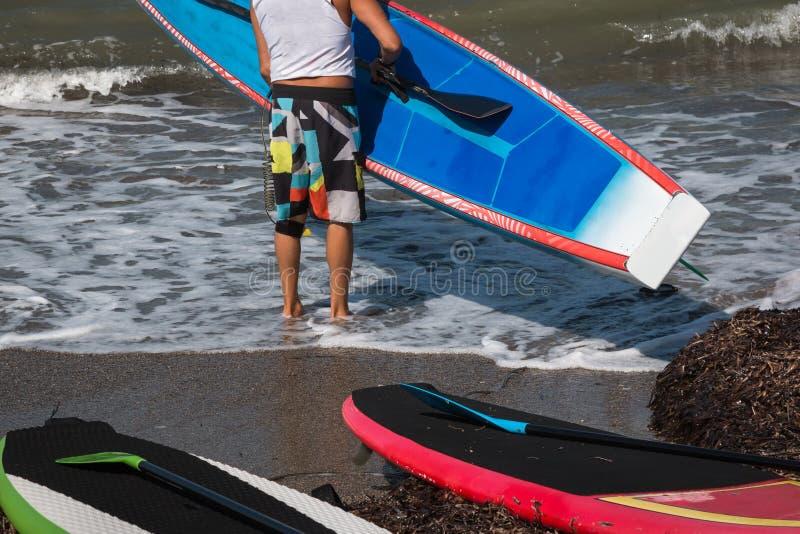 O homem pôs a placa na água na linha costeira imagem de stock