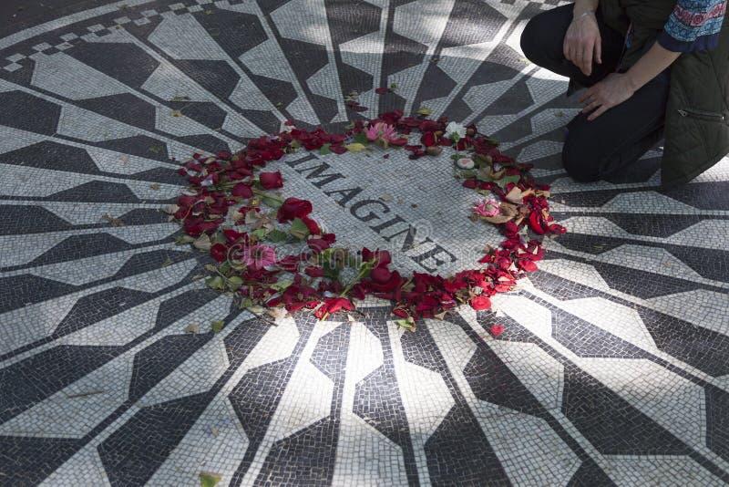 O homem paga o tributo ao lennon de john no memorial do mosaico no pa central imagens de stock royalty free