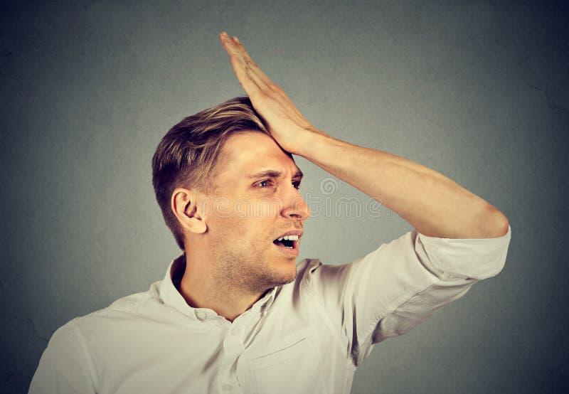 O homem parvo, golpeando a mão na cabeça que tem duh o momento lamenta imagens de stock royalty free