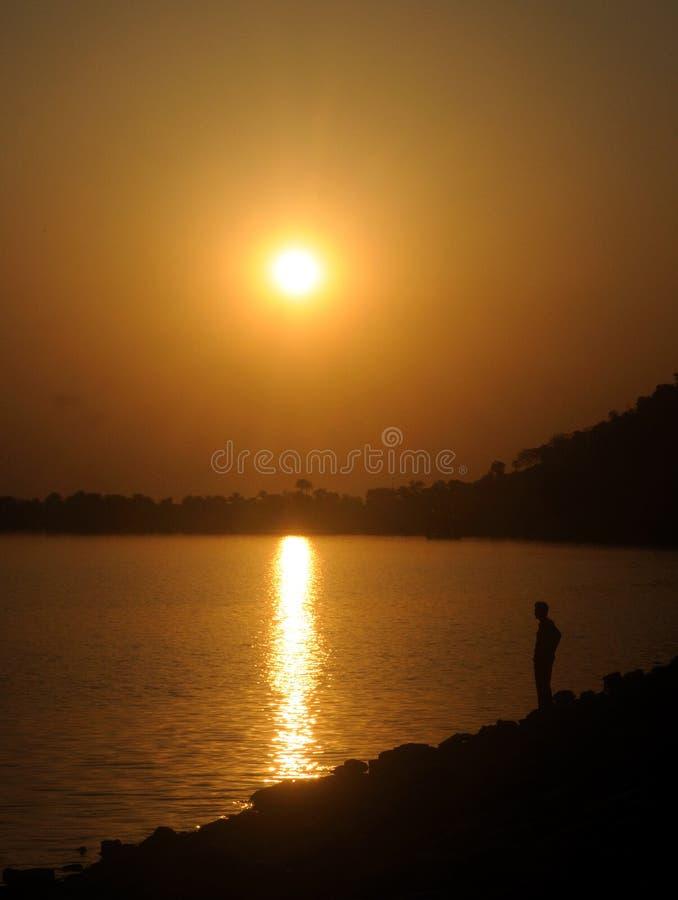 O homem pela silhueta do lago fotografia de stock royalty free