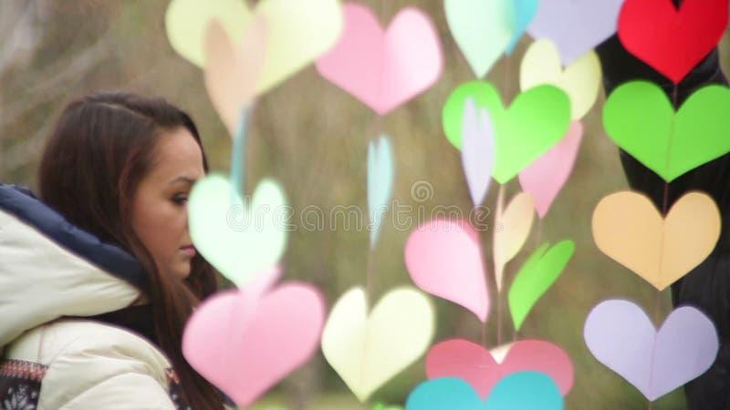 O homem pendura corações coloridos no dia de Valentim video estoque