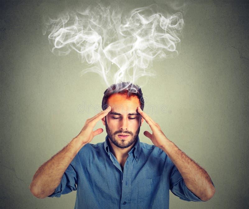 O homem pensa muito intensamente tendo a dor de cabeça imagens de stock