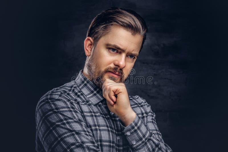 O homem pensativo da Idade Média com barba e o penteado vestido em uma camisa quadriculado levantam com mão no queixo fotos de stock royalty free