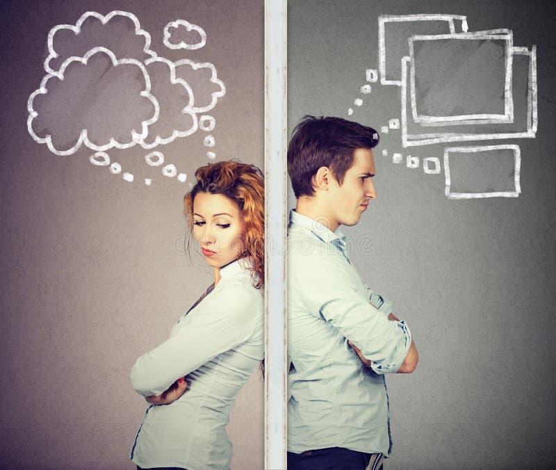 O homem pensativo e a mulher dos pares irritados separaram pela parede foto de stock