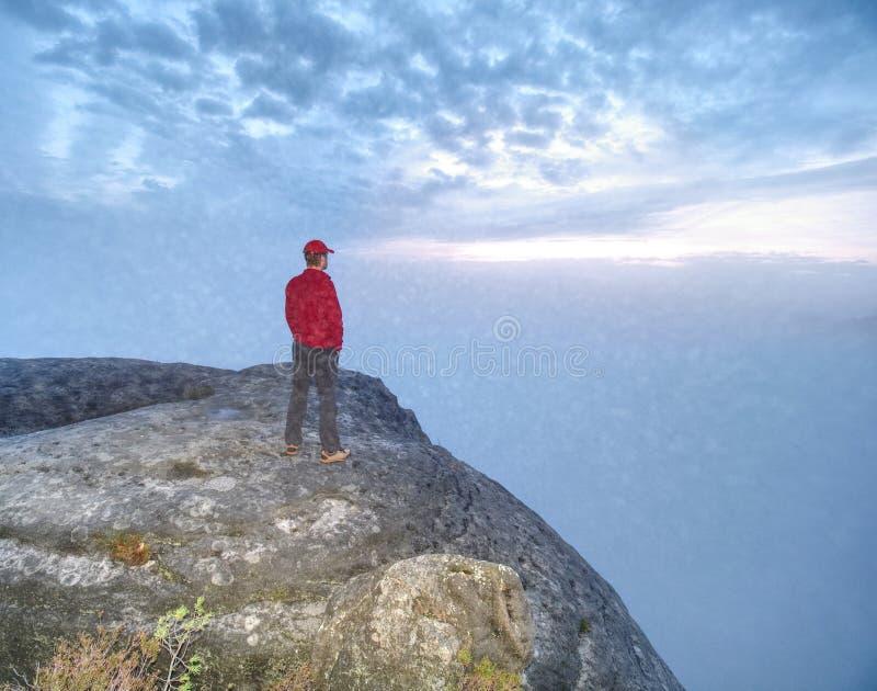 O homem perdeu em rochas grossas da névoa O caminhante escalou acima apenas à cimeira exposta imagem de stock royalty free