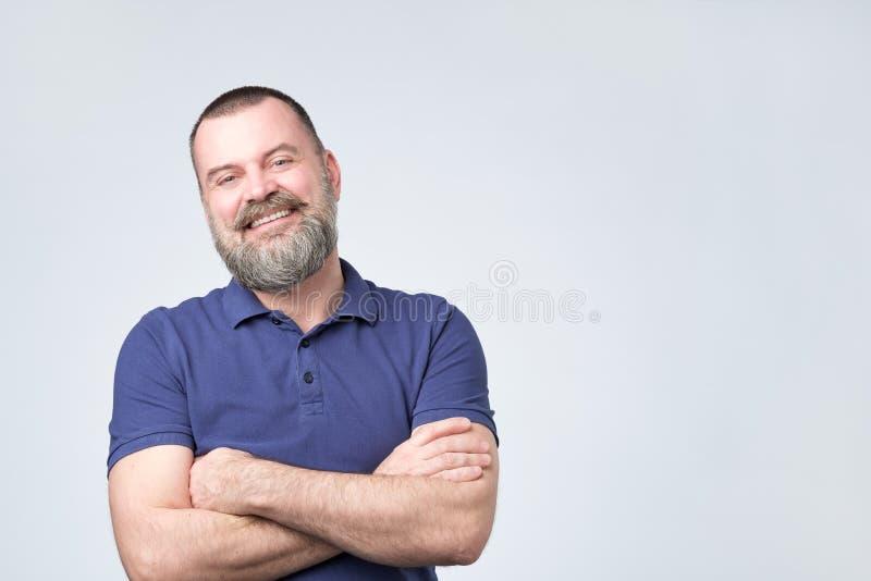 O homem positivo maduro com mão azul da terra arrendada do t-shirt do weairn da barba cruzou-se e olhando a câmera fotos de stock royalty free