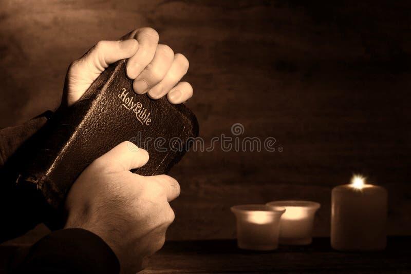 O homem Praying entrega a terra arrendada e a Bíblia velha de rebitamento fotografia de stock