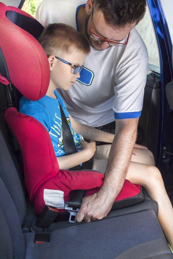 O homem prende um cinto de segurança a uma criança que se esteja sentando em um banco de carro no banco traseiro fotografia de stock