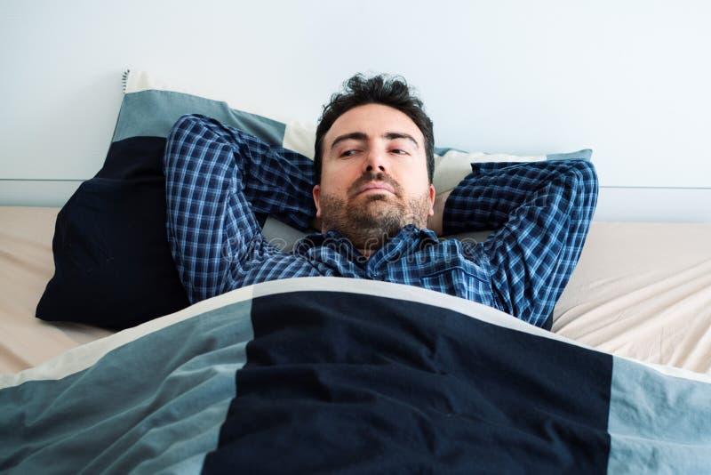 O homem preocupado não pode dormir pensando sobre problemas imagens de stock
