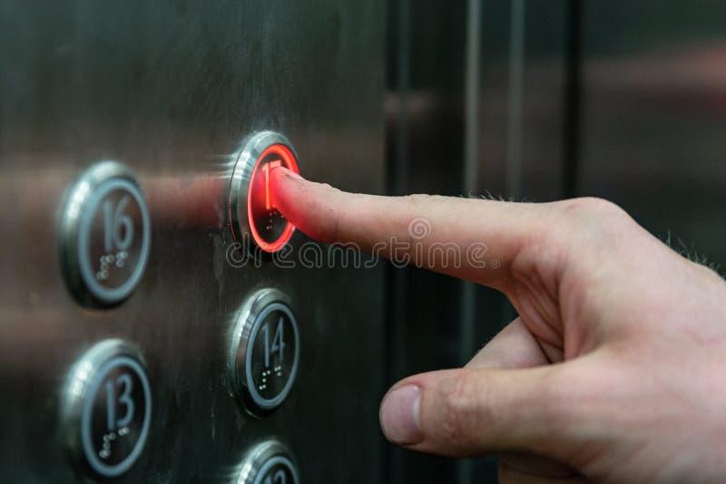 O homem pressiona o botão do elevador imagem de stock