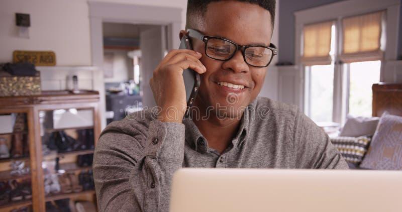 O homem preto com vidros fala no telefone que trabalha em seu portátil imagem de stock royalty free