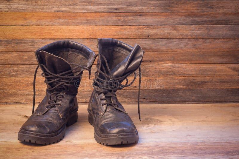 O homem preto de couro velho calça botas do tornozelo em um close-up de madeira da opinião dianteira do fundo fotos de stock