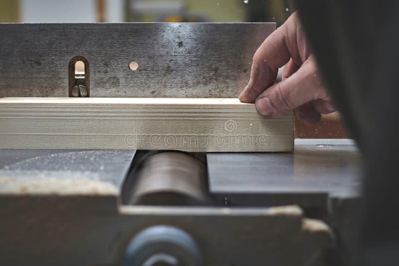 O homem processa a barra de uma árvore clara no plano de jointer imagem de stock
