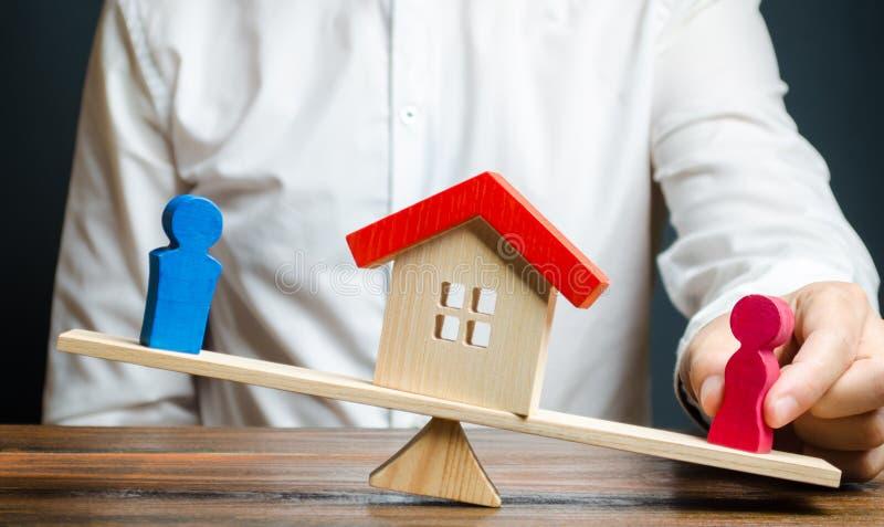 O homem promove figuras fêmeas para aumentar o equilíbrio das escalas em seu favor A separação de propriedade e de bens imobiliár fotos de stock royalty free