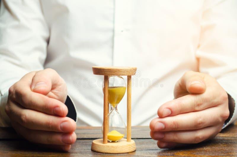 O homem protege a ampulheta Conceito do tempo de salvamento e do dinheiro Gestão de tempo Trabalho planeando Custo reduzido e car imagens de stock royalty free