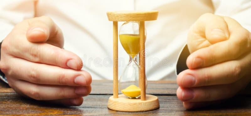 O homem protege a ampulheta Conceito do tempo de salvamento e do dinheiro Gest?o de tempo Trabalho planeando Custo reduzido e car imagem de stock