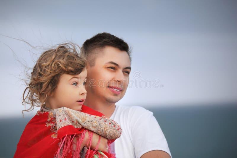 O homem protege a menina do vento no seacoast fotos de stock royalty free