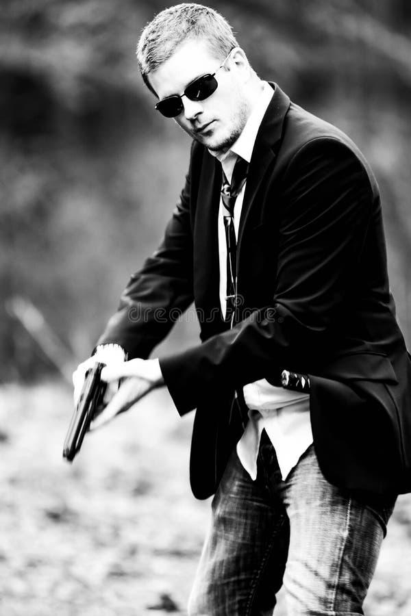 O homem puxa uma arma no carro imagens de stock
