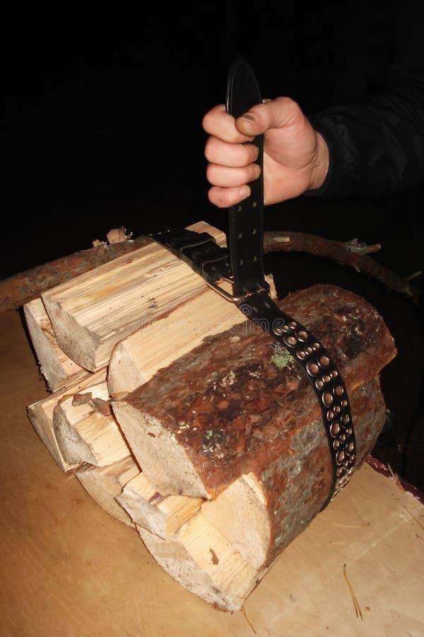 O homem puxou a correia de couro sobre os logs e guarda-os em sua mão fotos de stock royalty free