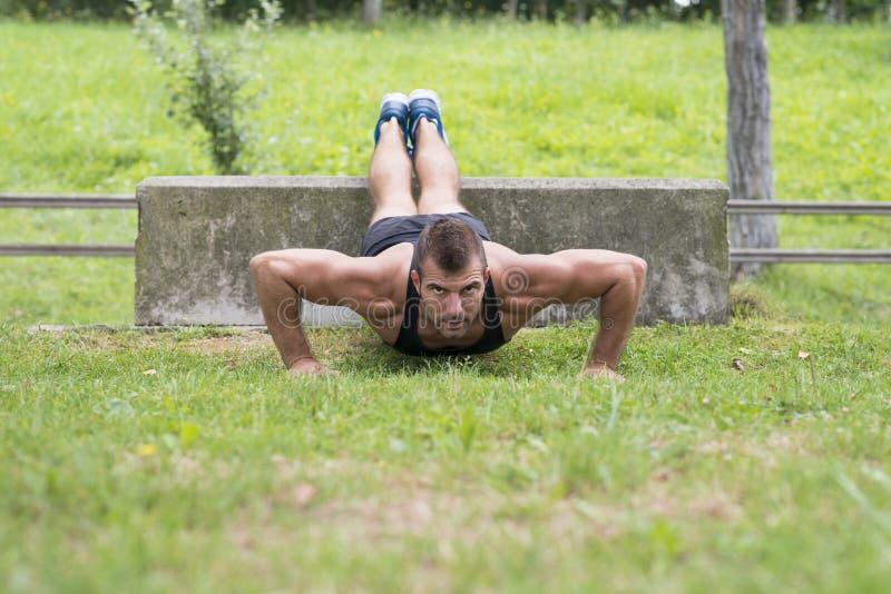 O homem que atlético fazer empurra levanta, exterior imagens de stock