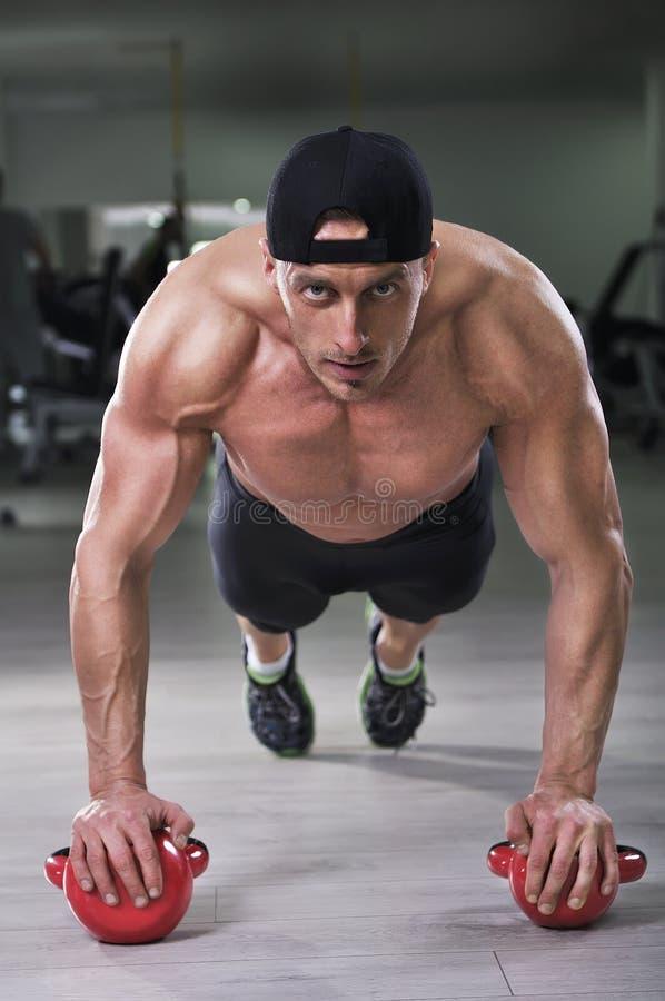 O homem que atlético poderoso considerável executar empurra levanta com sino da chaleira fotografia de stock