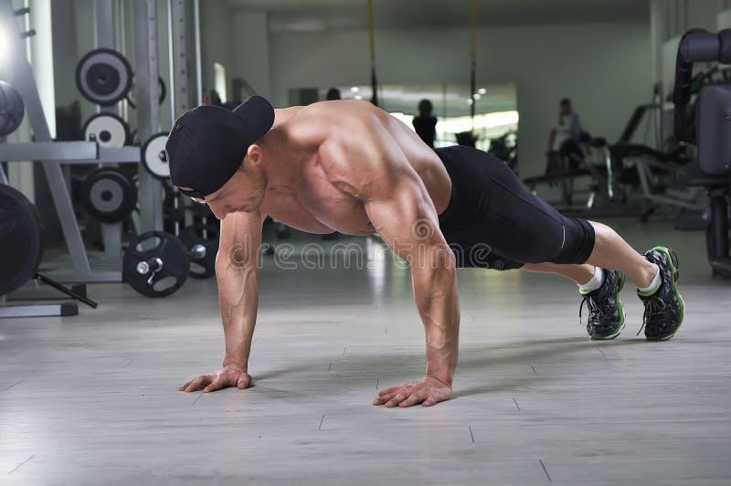 O homem que atlético poderoso considerável executar empurra levanta no gym foto de stock royalty free