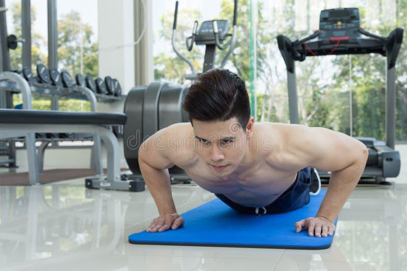 O homem que considerável a aptidão que exercita fazendo empurra levanta como parte do treinamento do halterofilismo no fitness ce fotografia de stock royalty free